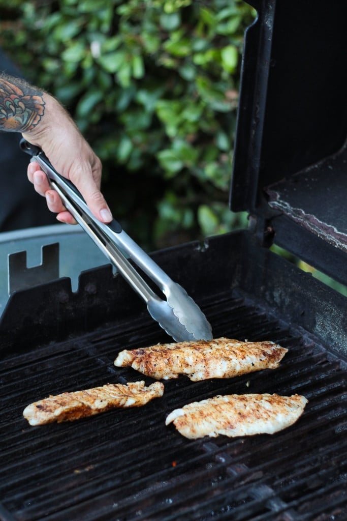 seasoned fish fillets being grilled on an outdoor grill for making healthy grilled fish tacos recipe