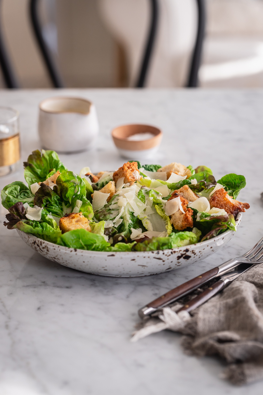 A bowl of Caesar salad on a marble dining table