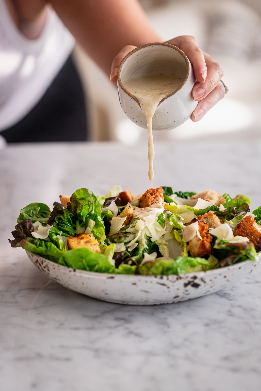 A woman pouring dressing over a bowl of Caesar salad