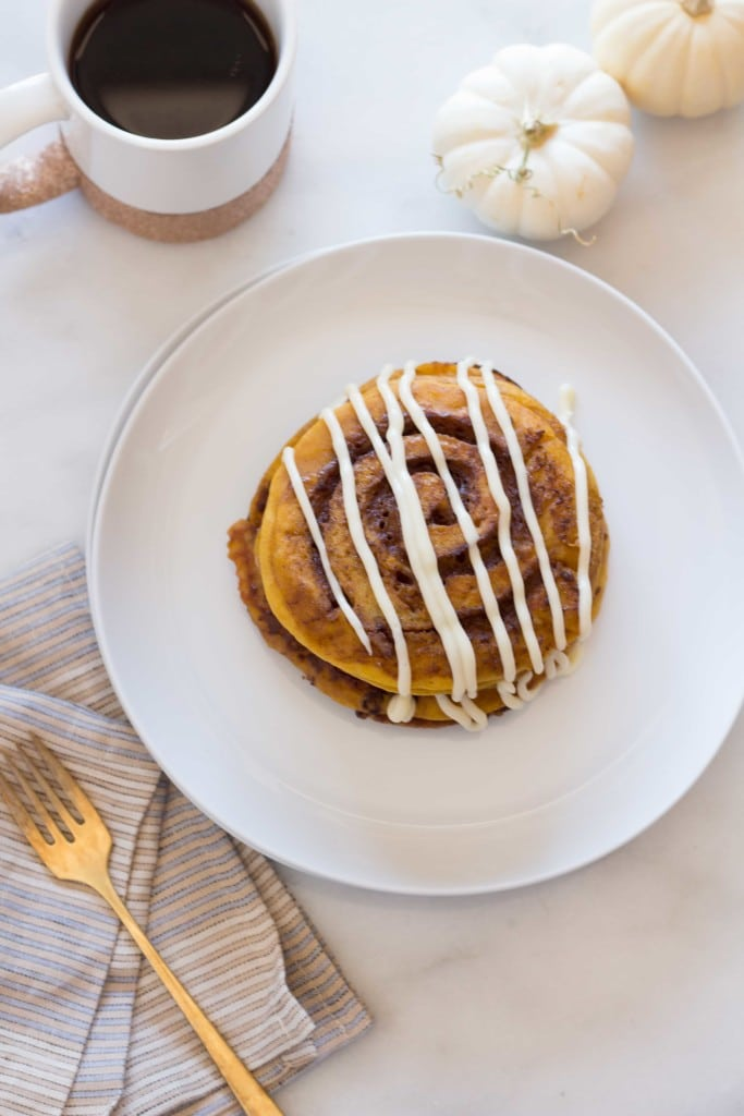 Pumpkin Cinnamon Roll Pancakes drizzled with cream cheese glaze on a white plate