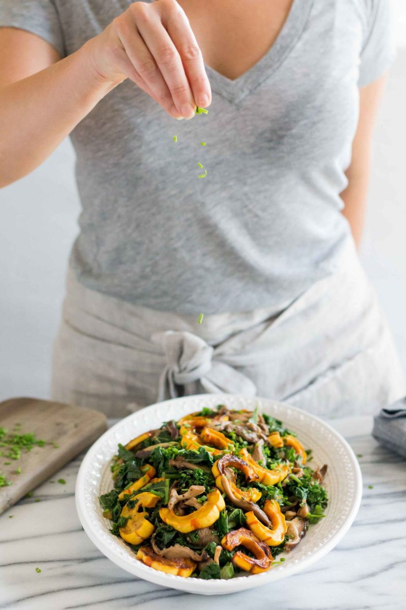 a woman sprinkling chopped chives over a platter of warm kale delicata squash salad