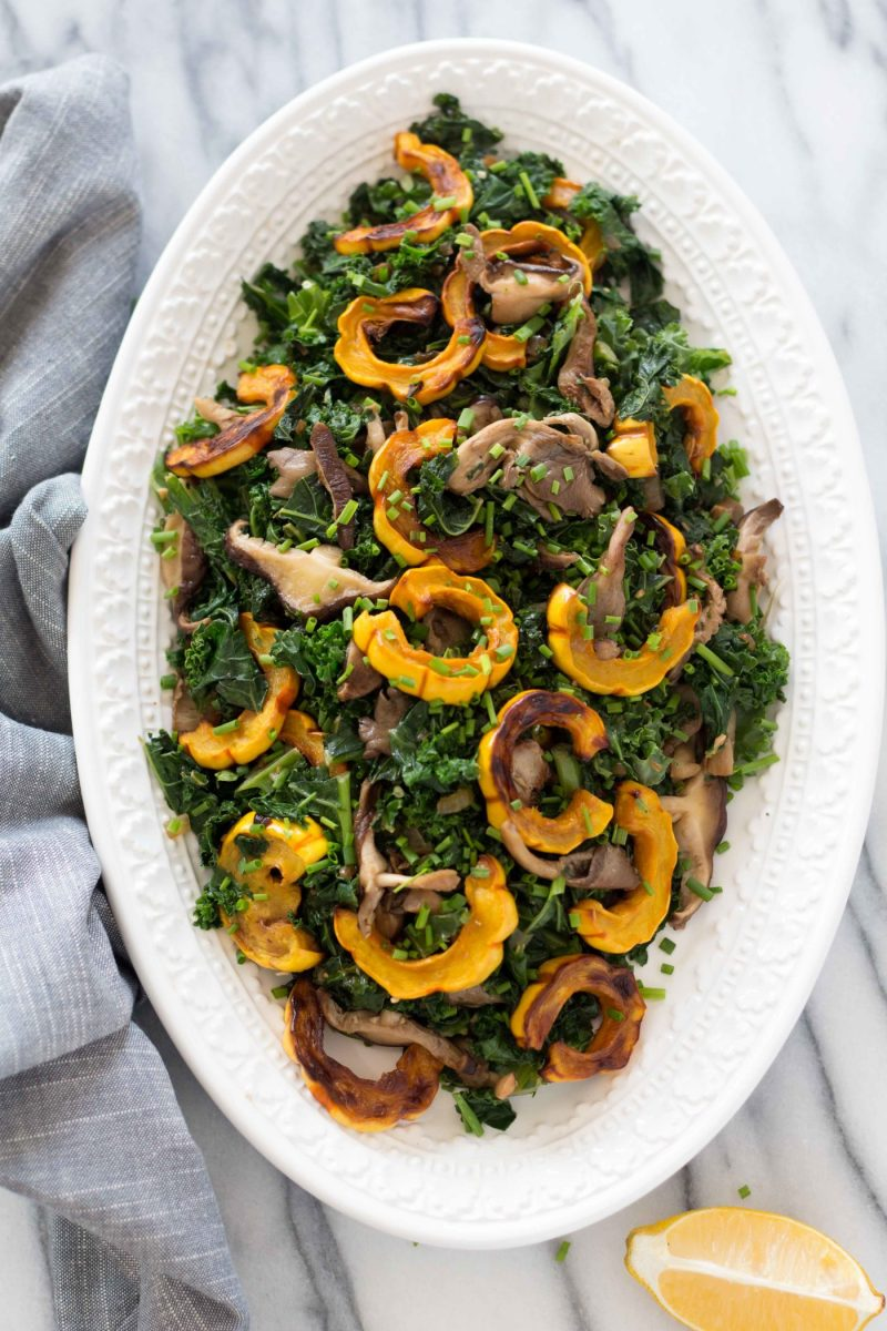 overhead shot of warm kale salad with roasted delicata squash and wild mushrooms