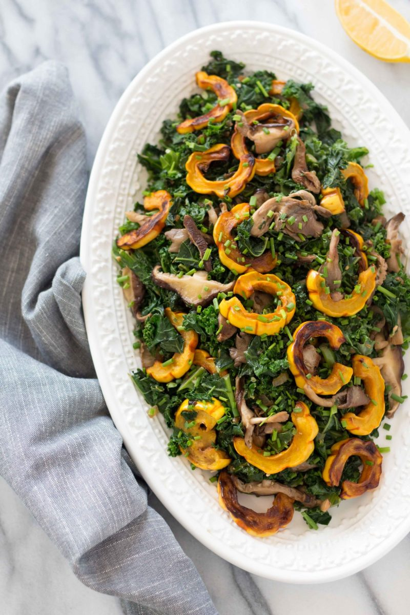 overhead shot of a platter with warm kale delicata squash salad