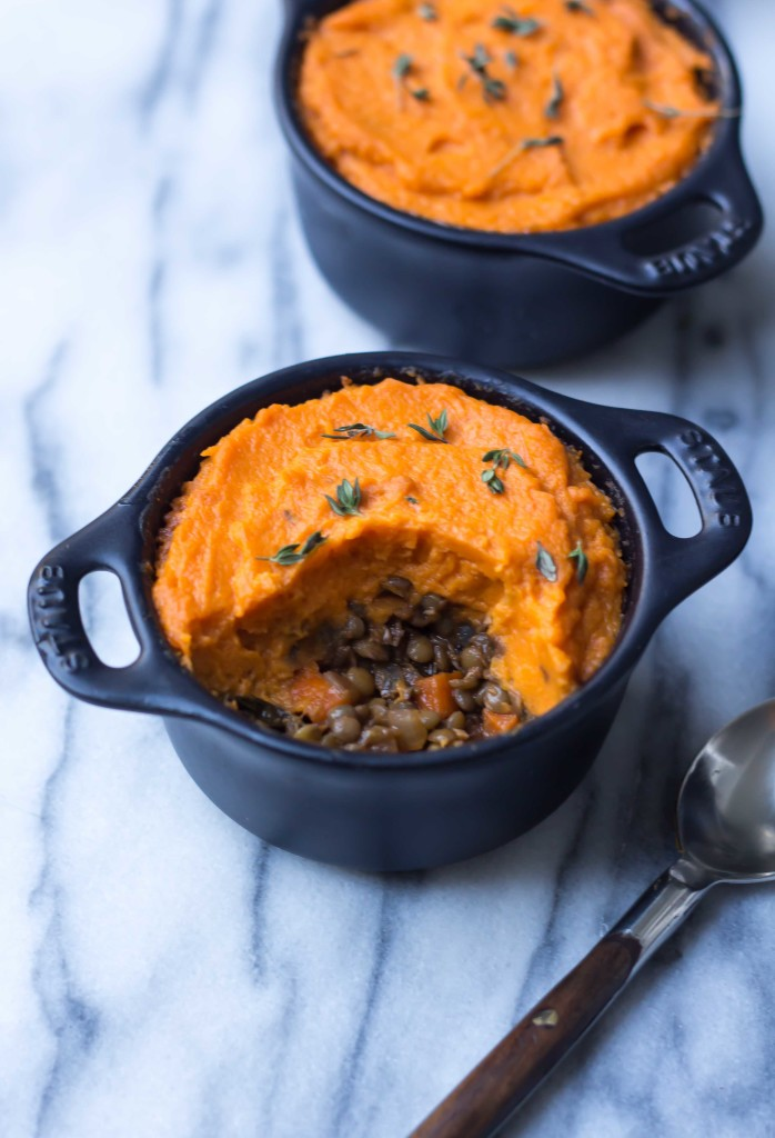 a half eaten vegetarian shepherd's pie in a small black ramekin revealing a savory lentil ragu under the creamy sweet potato topping