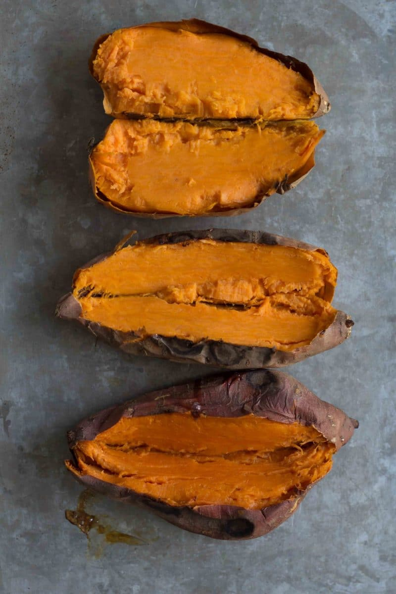 three backed sweet potatoes split open, cooling on a baking tray