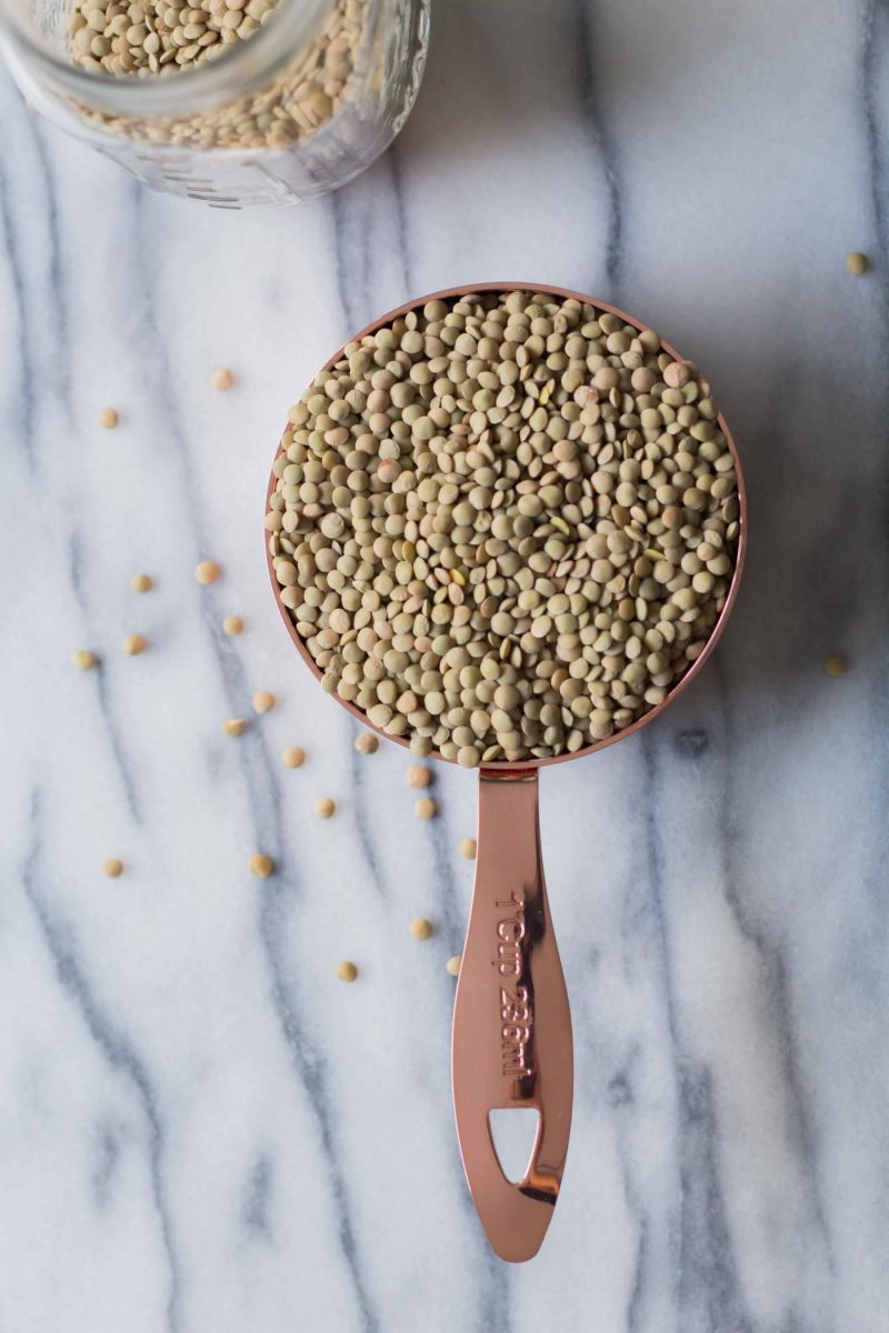 dried lentils in a copper measuring cup placed on a marble counter top