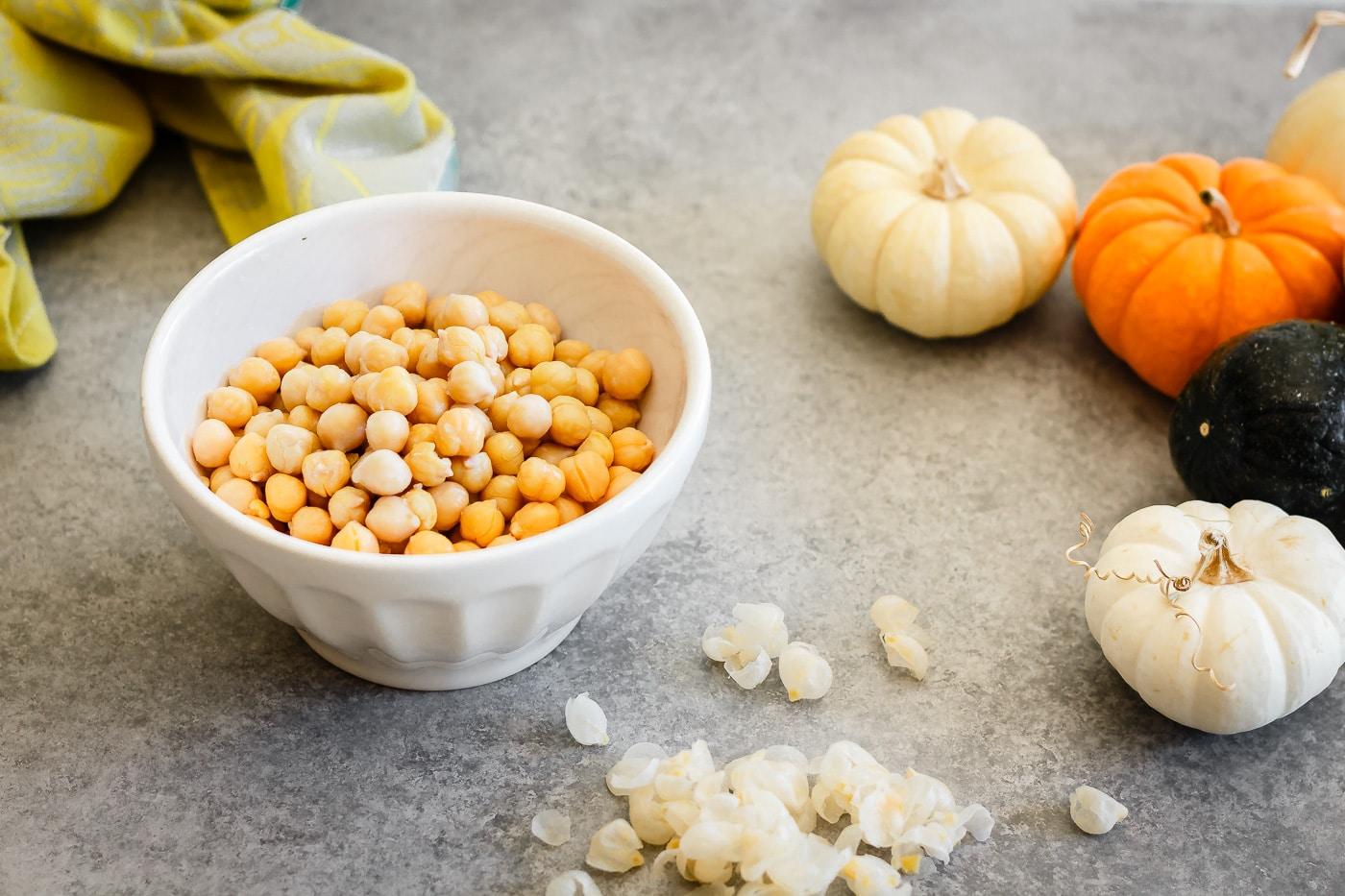 peeled canned chickpeas in a small white bowl with the peeled shells lying on the side