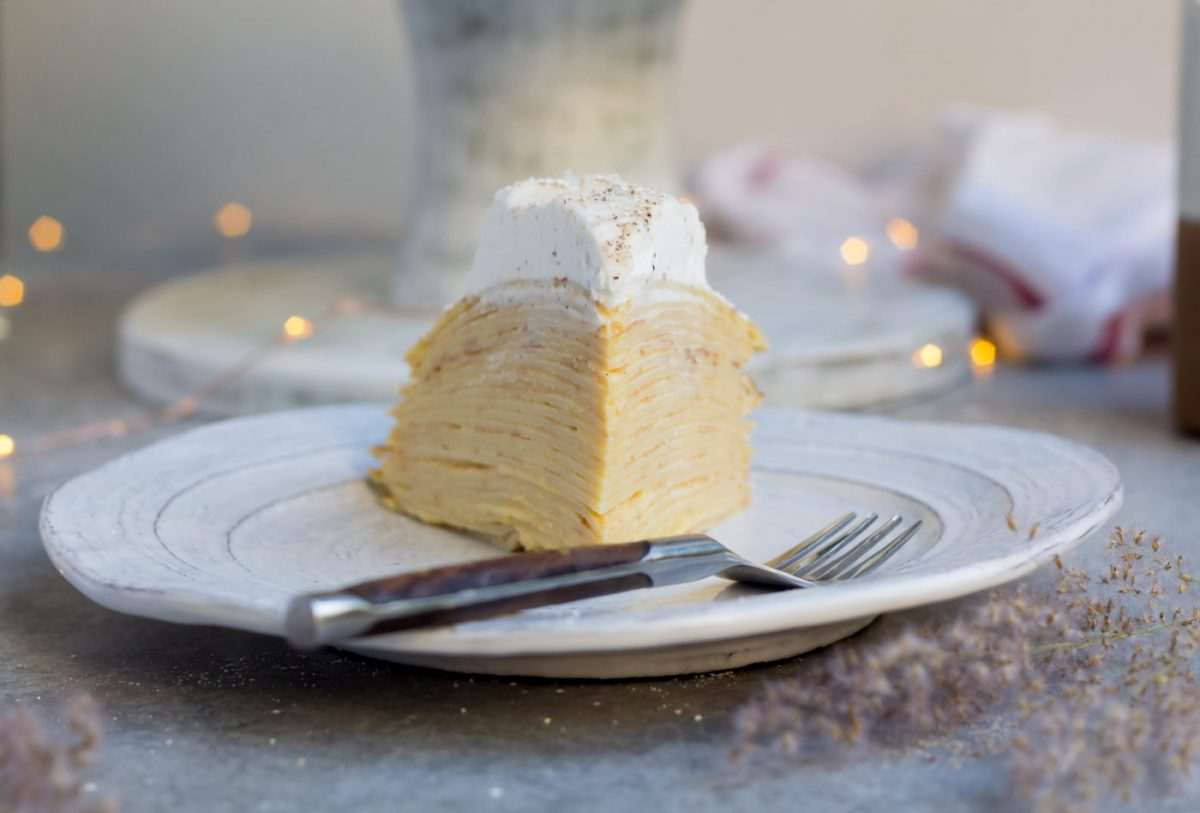 a slice of Eggnog Mille Crepe Cake with eggnog pastry cream on a white plate