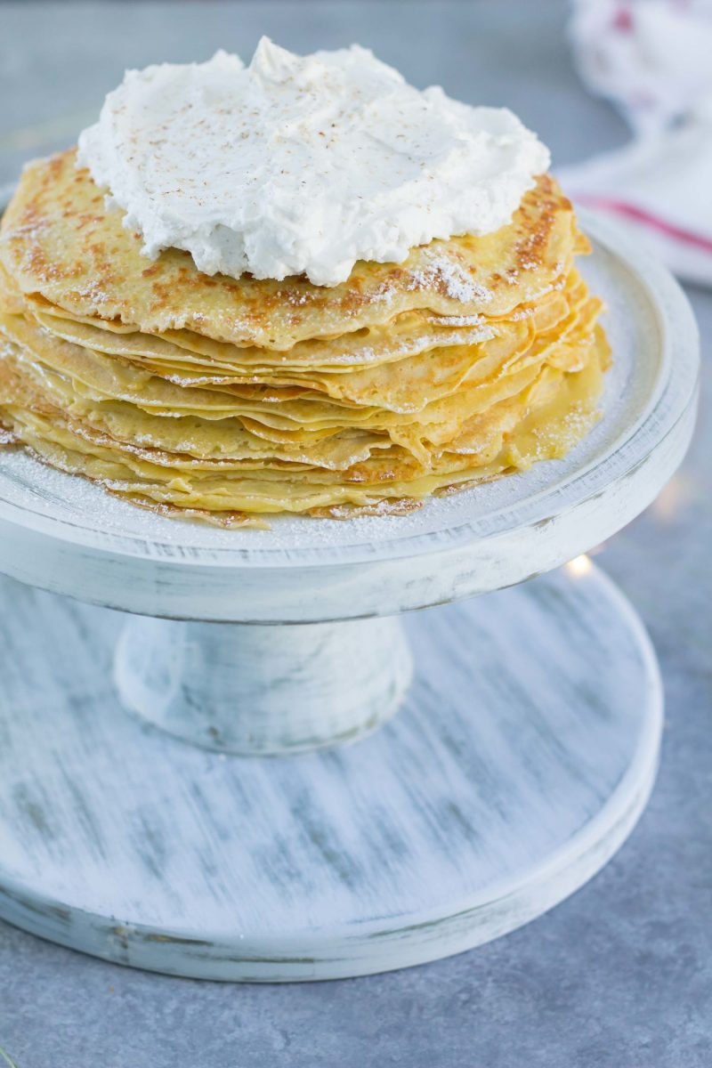 Easy Eggnog Crepe Cake with eggnog pastry cream on a white cake stand