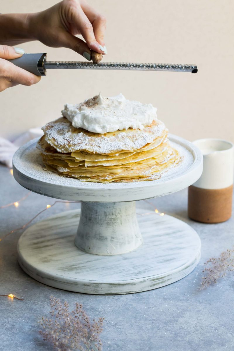 fresh nutmeg being grated on top of a Eggnog Crepe Cake