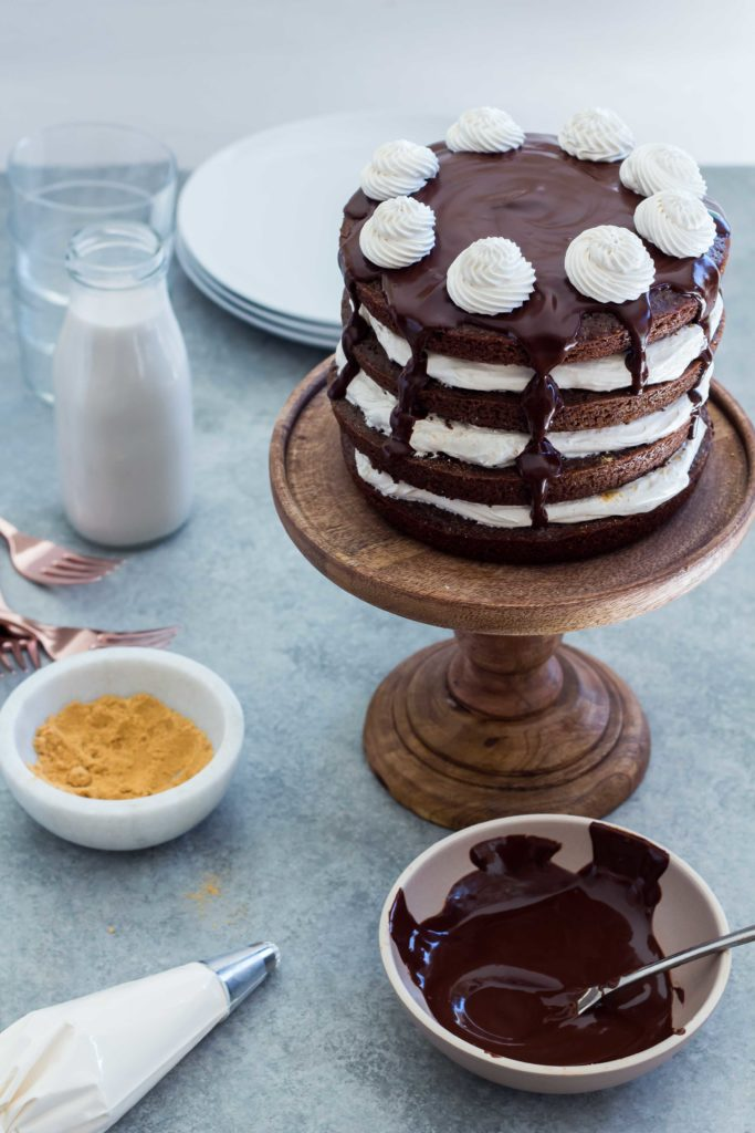 a tall Chocolate S'mores Layer Cake with Chocolate Ganache Topping on a wooden cake stand