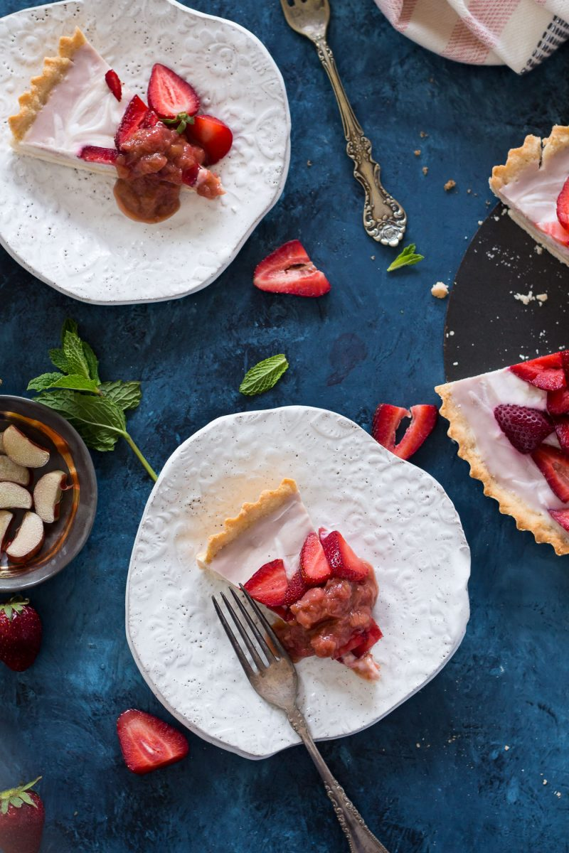two slices of Dairy-free Strawberry Vanilla Yogurt Tart served with fresh strawberries and rhubarb compote