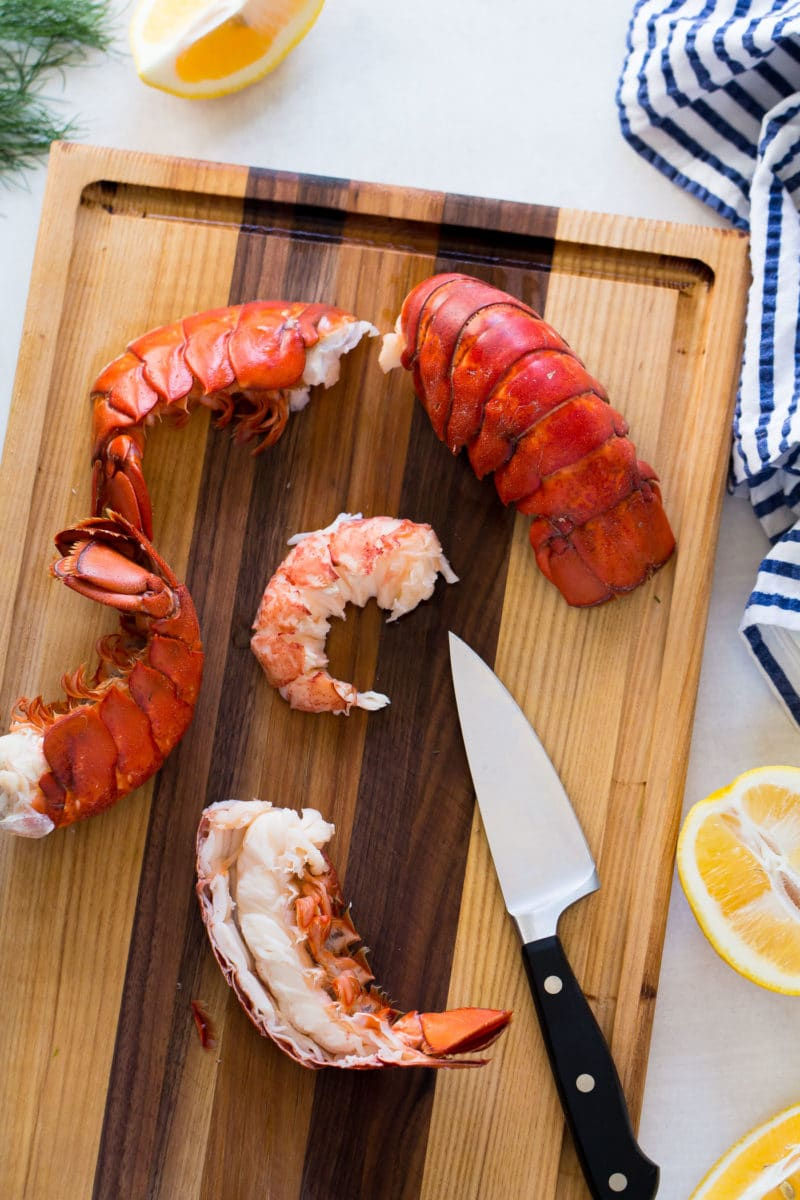steamed lobster being peeled on a wooden chopping board