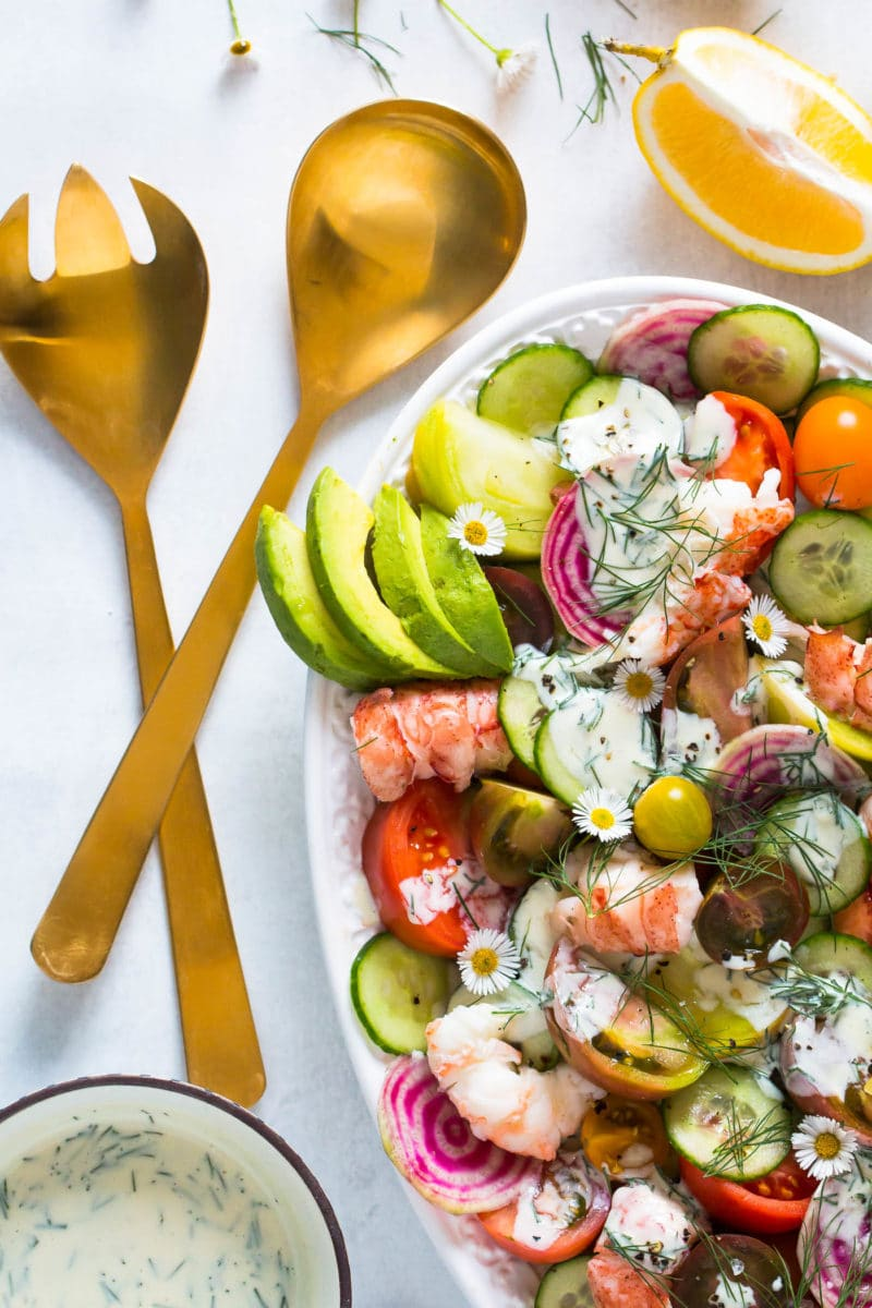 overhead shot of a salad platter with Heirloom Tomato Lobster Salad drizzled with buttermilk dressing