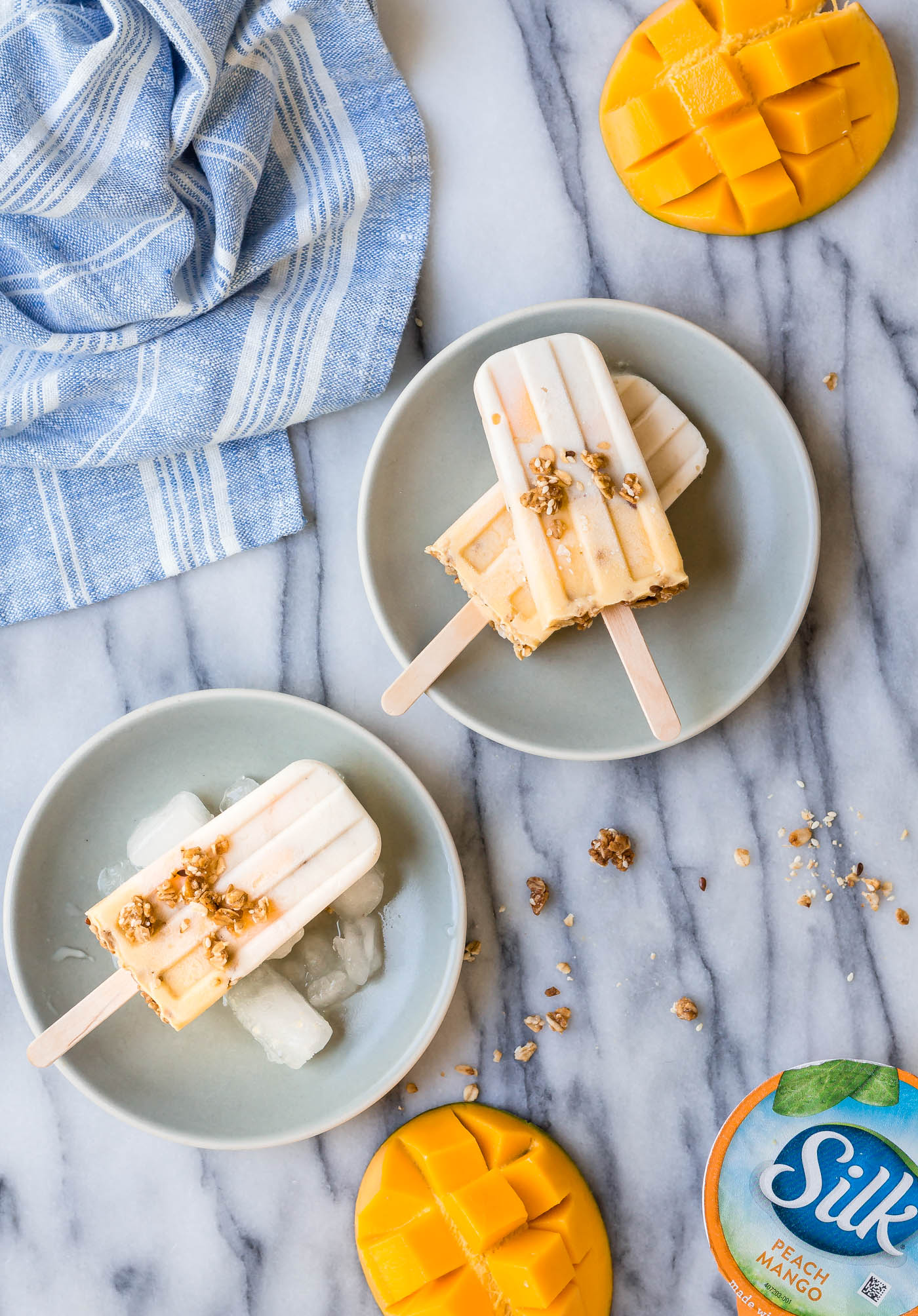 stacked dairy-free Vanilla Mango Popsicles served on plates with granola and fresh mango on the side