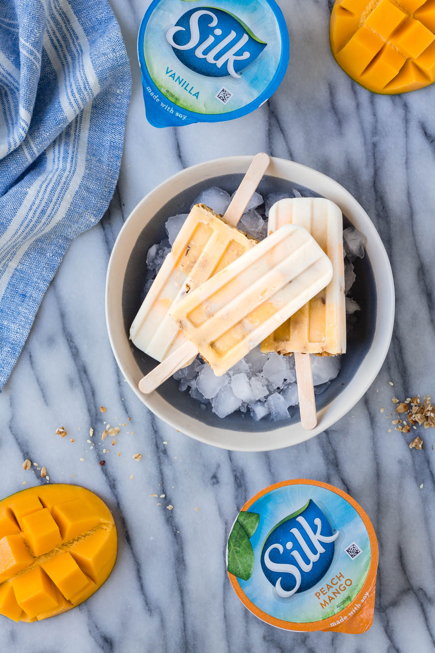 overhead shot of three gluten-free dairy-free Vanilla Mango Popsicles with Silk yogurt containers in the background