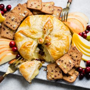 close up of Cranberry Maple Pecan Baked Brie with wedge removed