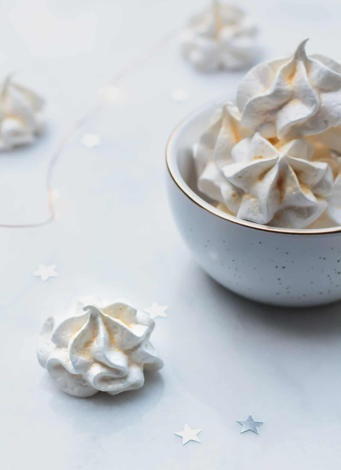 Champagne meringue with gold sugar and bowl of meringues