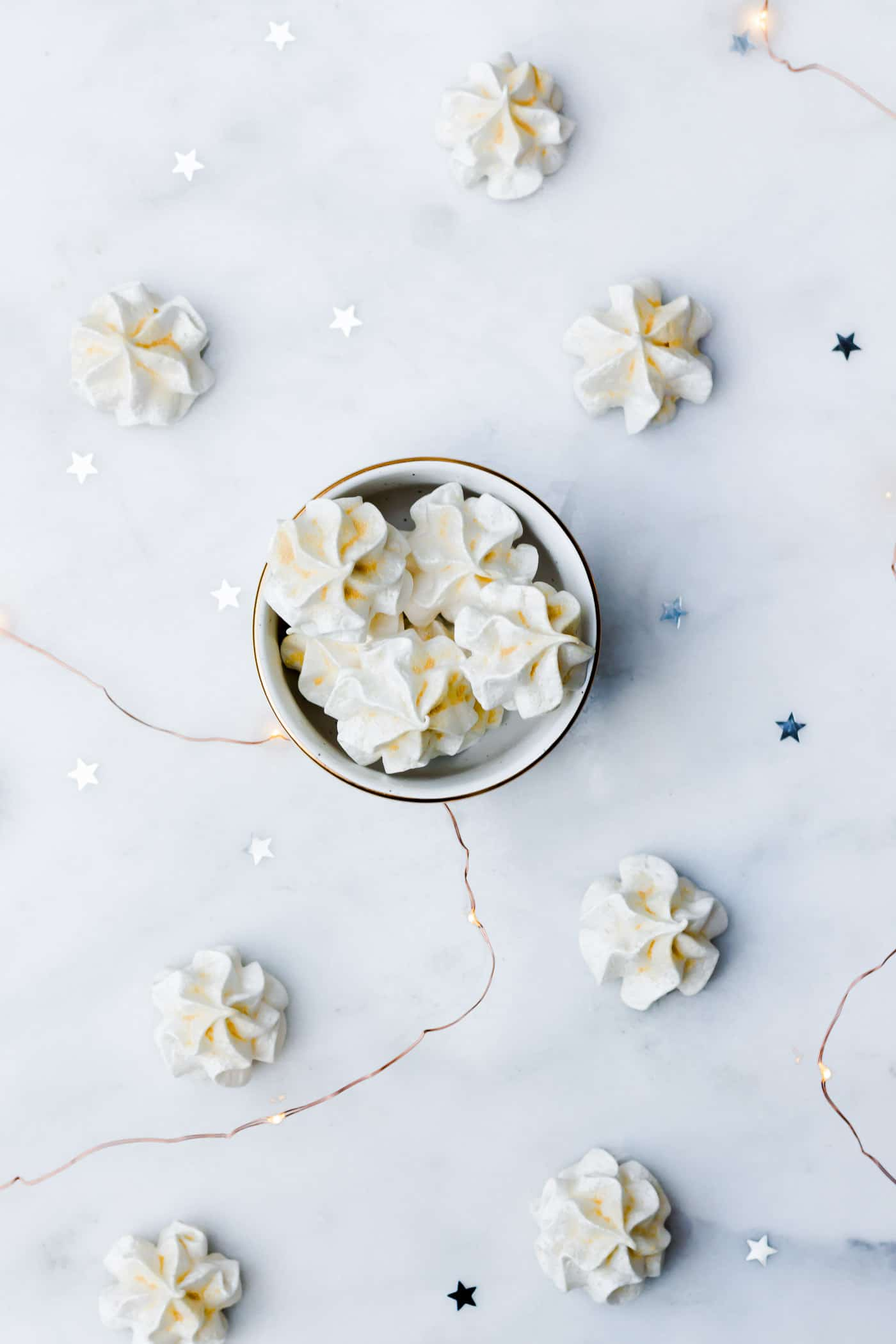 Champagne meringues scattered on a marble platter with copper string lights and silver star confetti