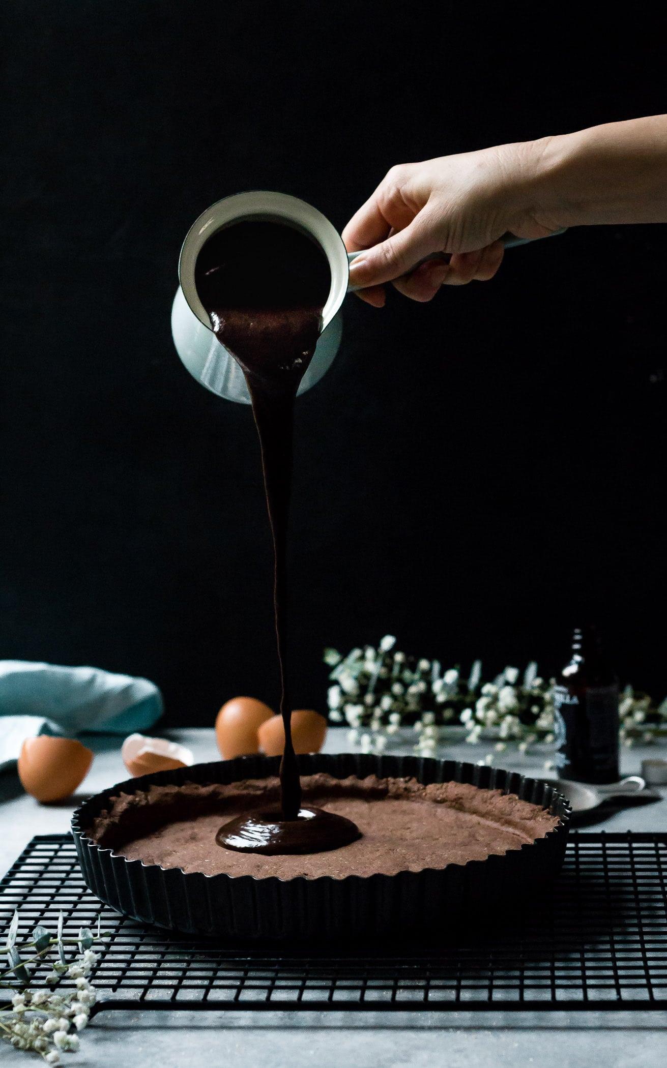 chocolate custard being poured into dark chocolate tart
