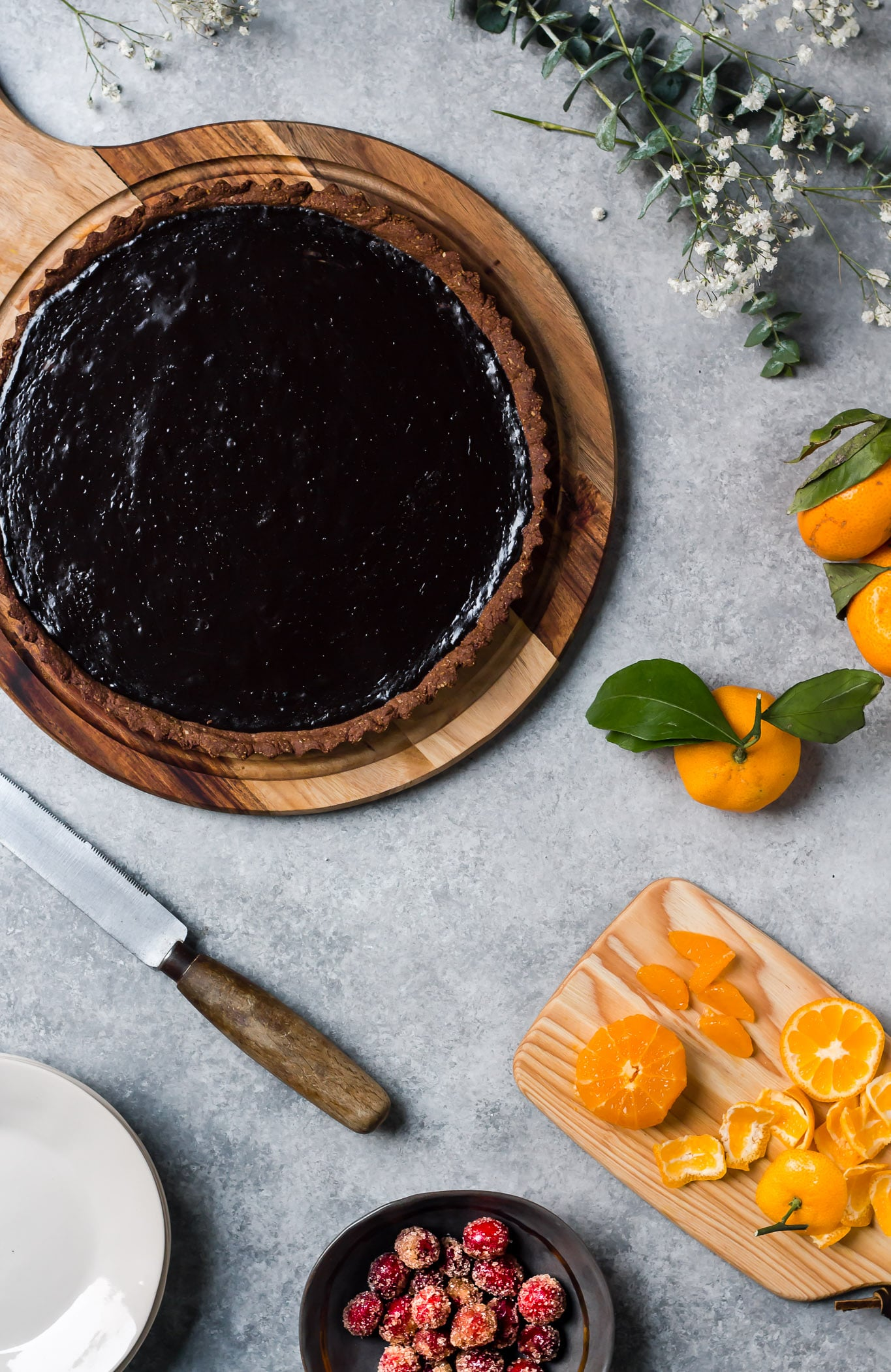 whole dark chocolate tart with bowl of cinnamon sugared cranberry and cut mandarins
