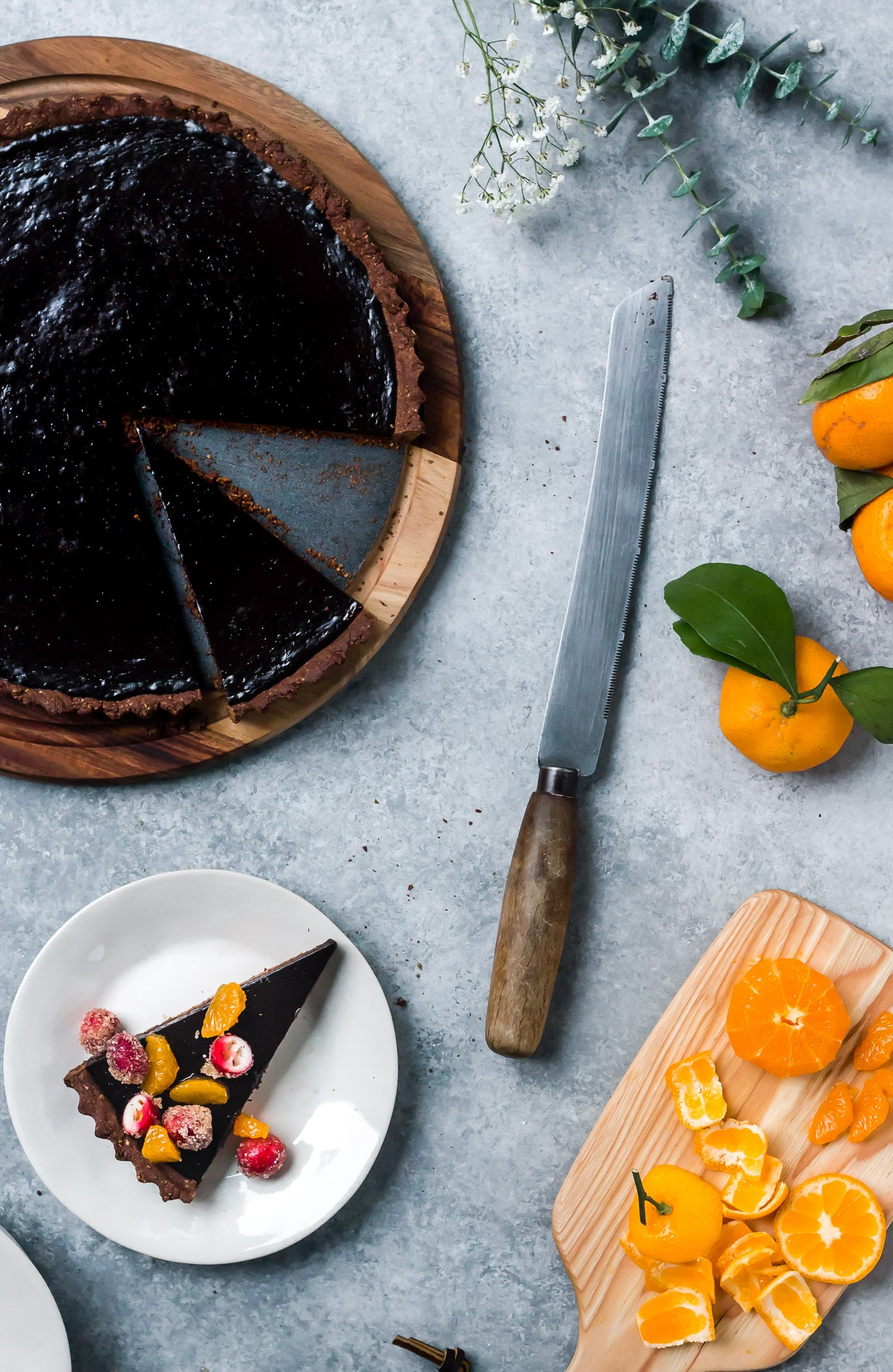 sliced dark chocolate tart topped with sugared cranberries and satsumas