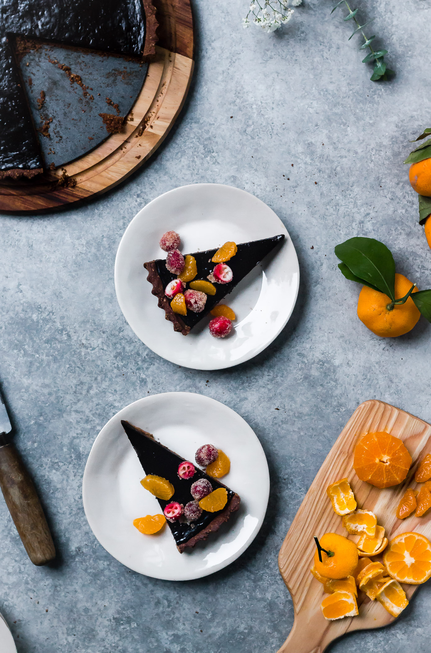 slices of dark chocolate tart with sugared cranberry and satsumas