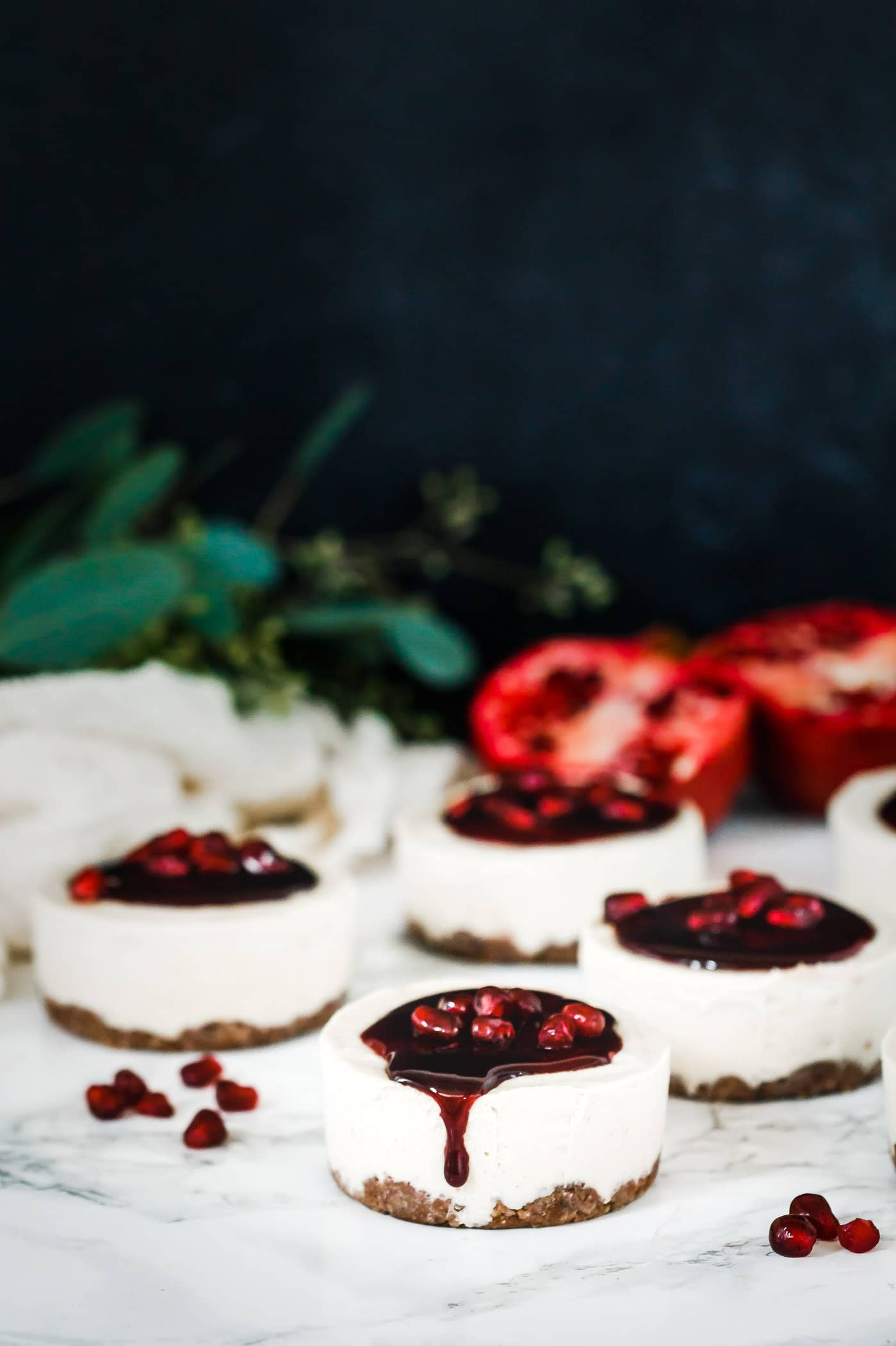 Front view of Vanilla Bean Pomegranate Mini Cheesecakes with glaze dripping off