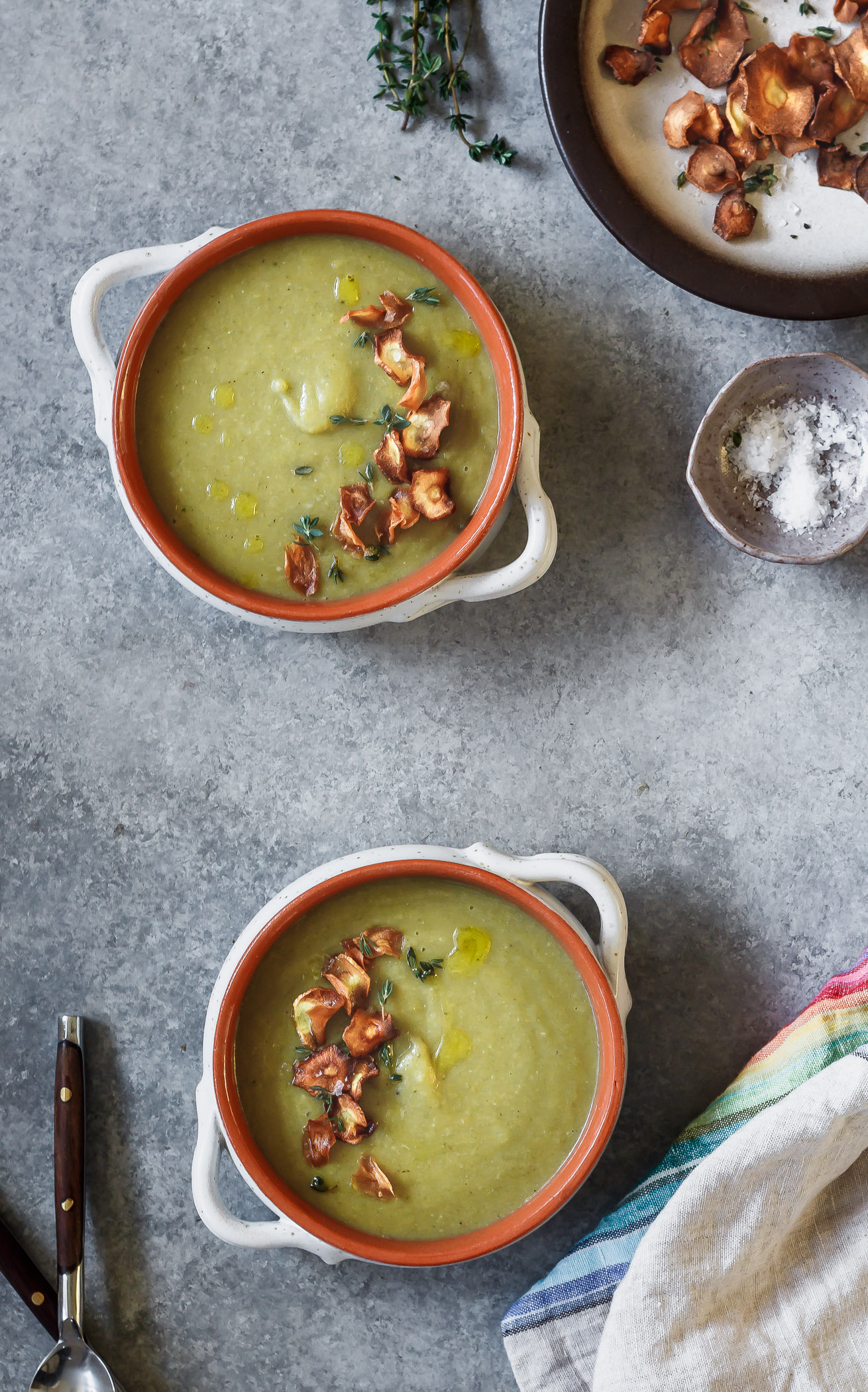Two bowls of artichoke soup with parsnip chips