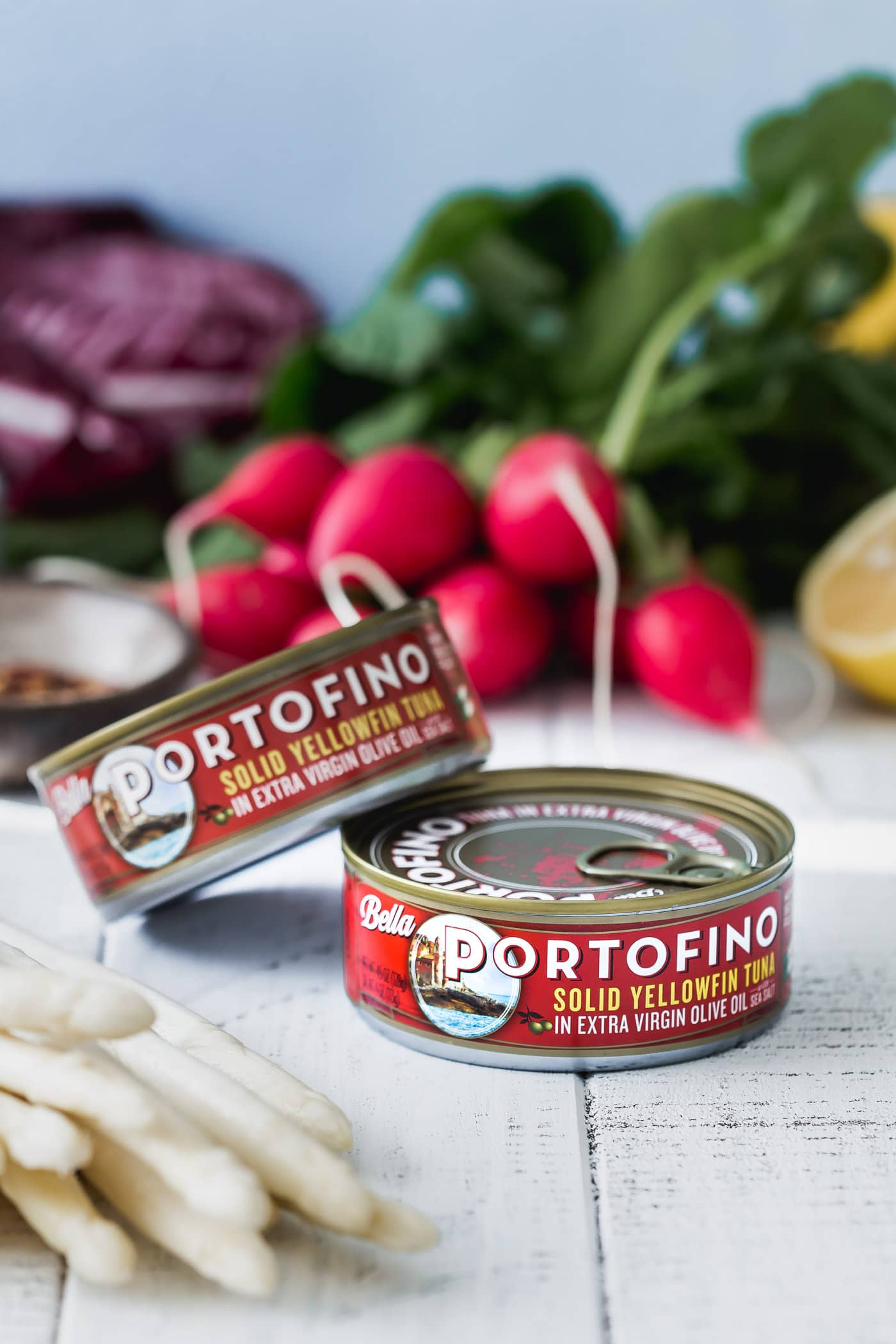 Cans of Bella Portofino Tuna with fresh produce behind