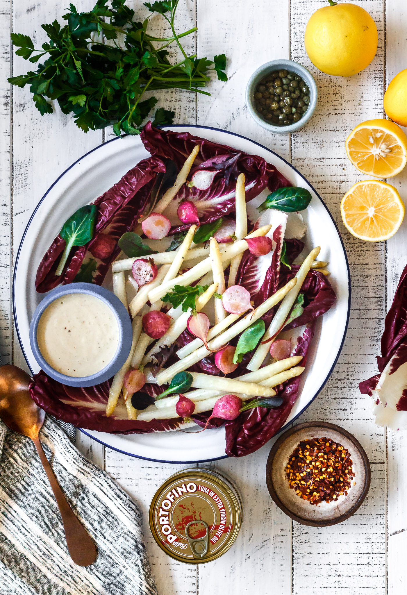 Meyer Lemon & Chile Tonnato Sauce in a bowl next to platter of white asparagus, treviso and roasted radish