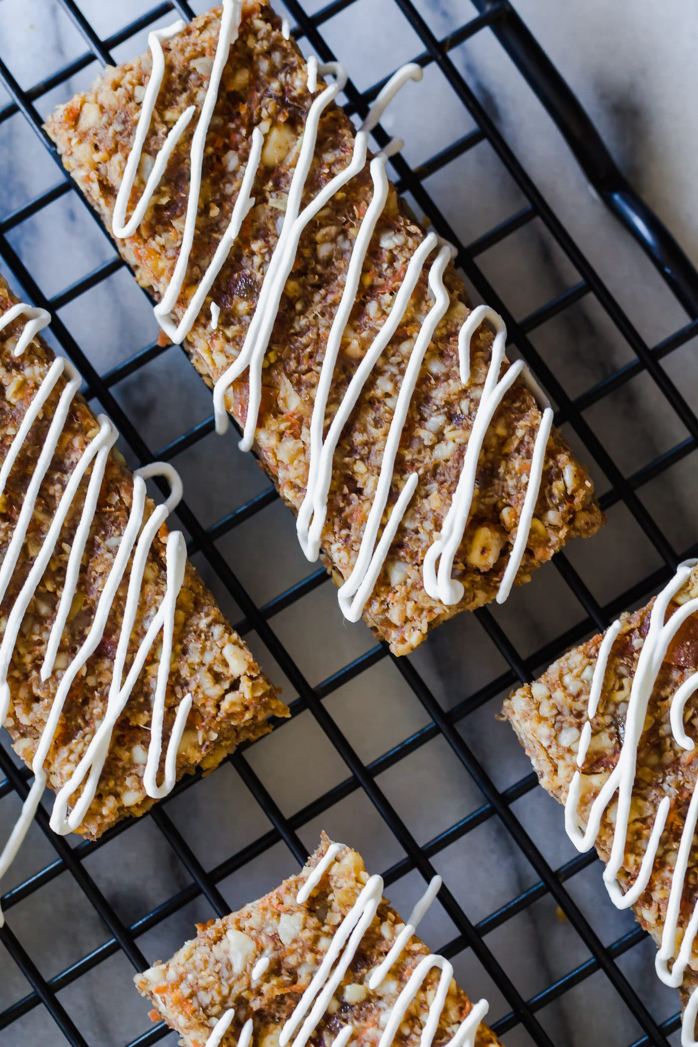 Healthy Vegan Carrot Cake Breakfast Bars on cooling rack with maple coconut icing