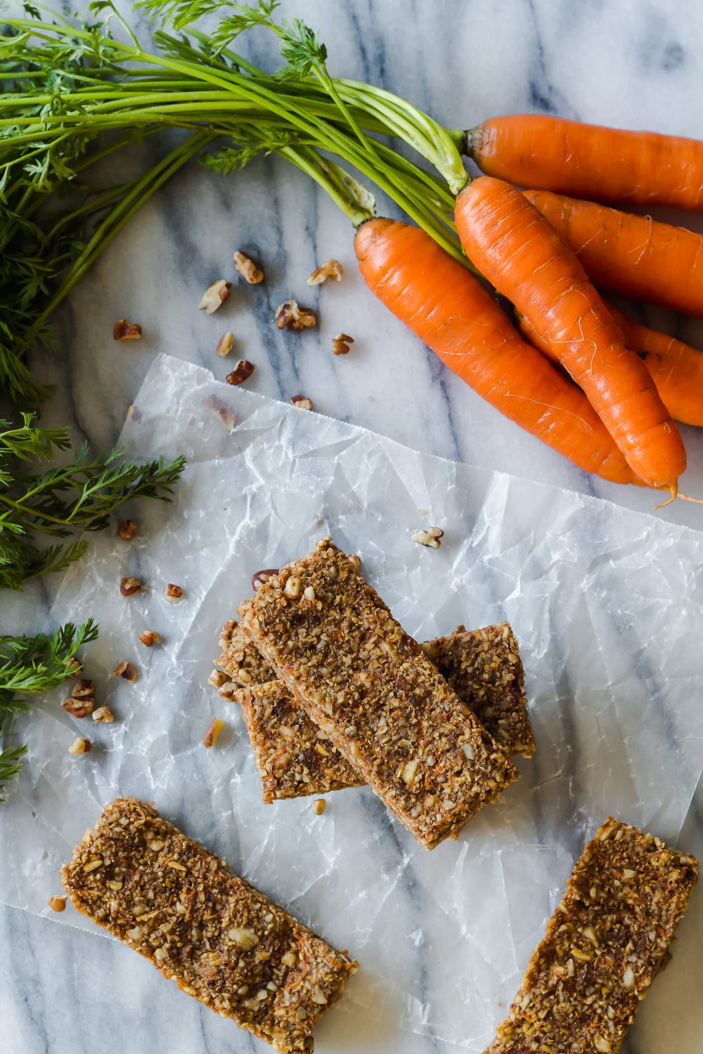 stacked Carrot Cake Breakfast Bars on cooling rack with maple coconut icing next to a bunch of carrots