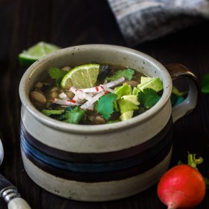 A mug of Farro and White Bean Posole Verde with toppings