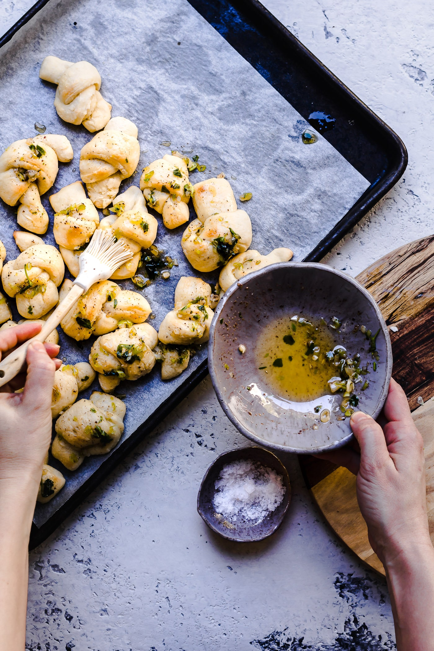 garlic knots being brushed with browned butter