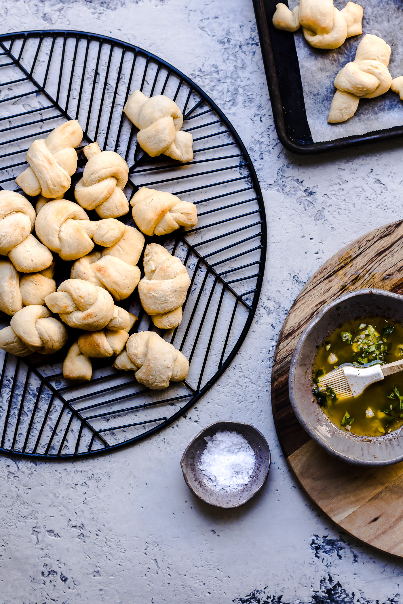 browned butter green garlic knots on a cooling rack with butter mixture in a bowl
