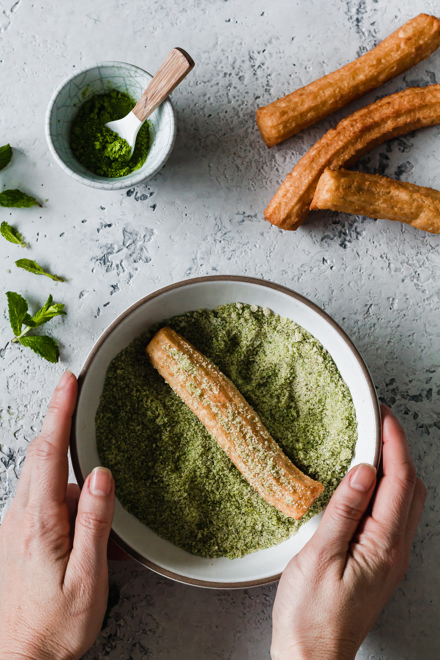 Rolling churros in matcha mint sugar