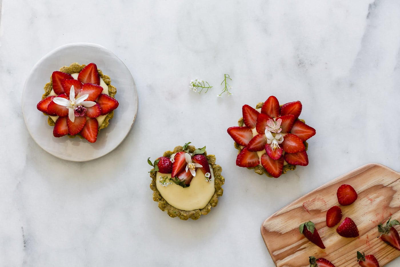 Gluten-free Pistachio Strawberry Tartlets filled with pastry cream on a marble countertop