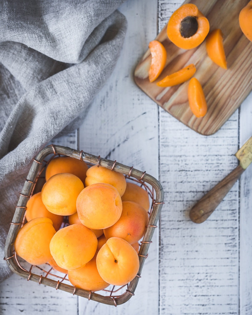 a small wire basked with fresh apricots nexts to a chopping board with a cut up apricot