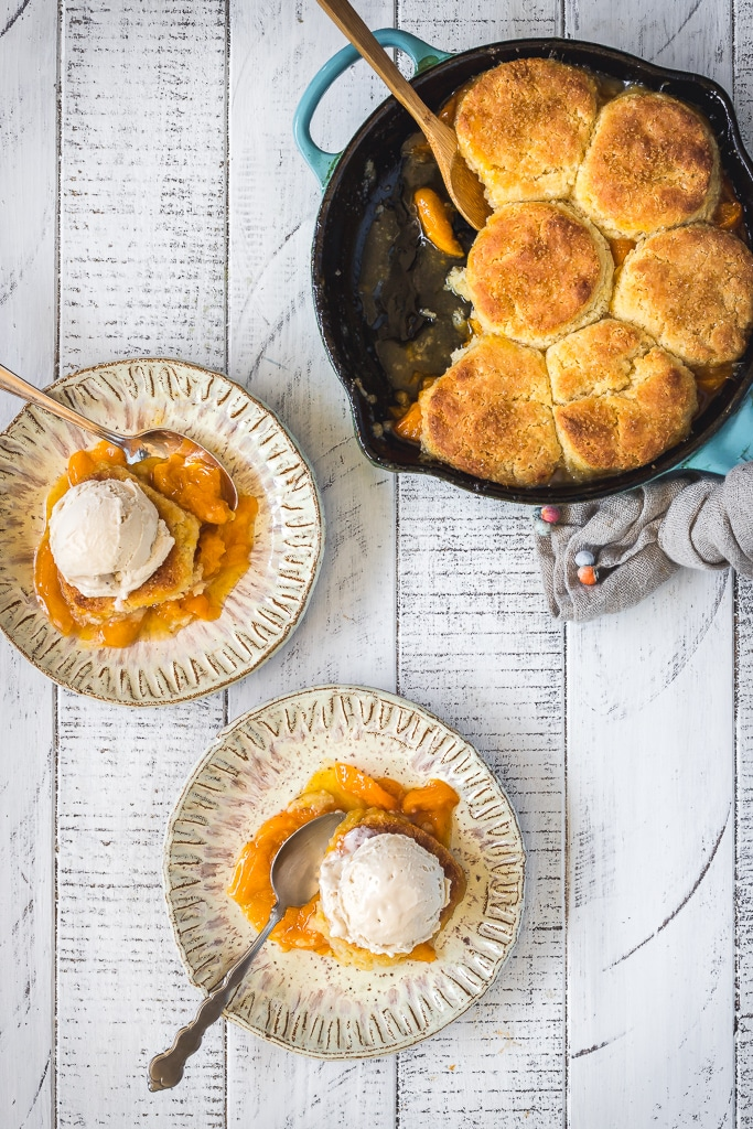 overhead shot of two plates of gluten-free Apricot Cobbler served with vanilla ice cream with a blue skillet in the background