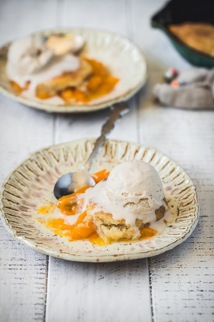 side view of a serving of Apricot Skillet Cobbler on a rustic plate with a silver spoon on the side