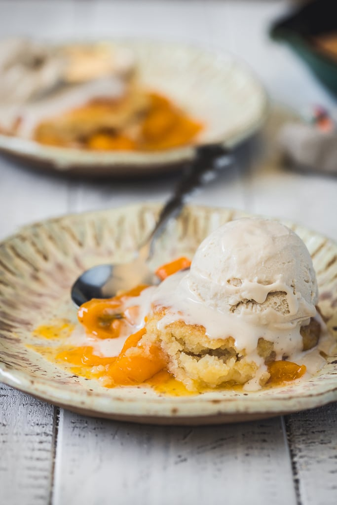 side view of a serving of apricot skillet cobbler served with vanilla ice cream