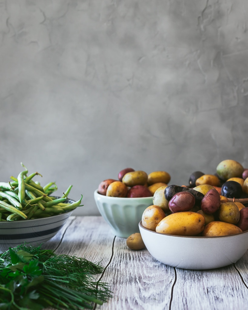 baby potatoes and green beans on a rustic wooden table