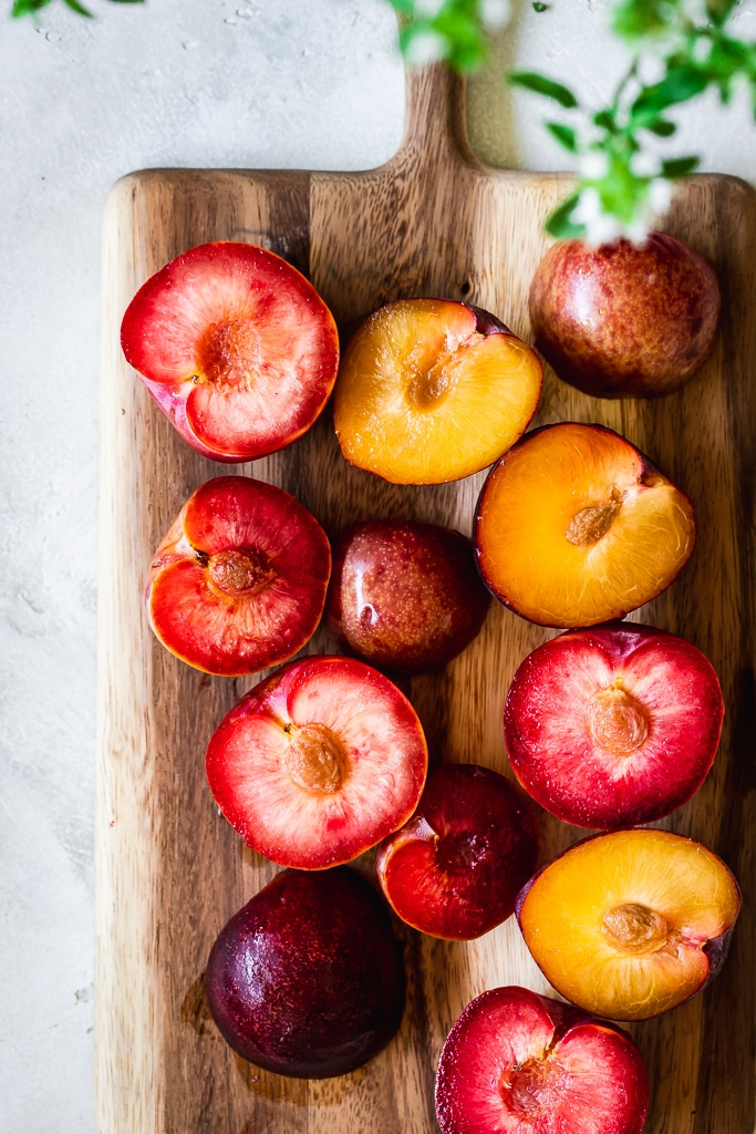 halved red and yellow plums on a wooden cutting board
