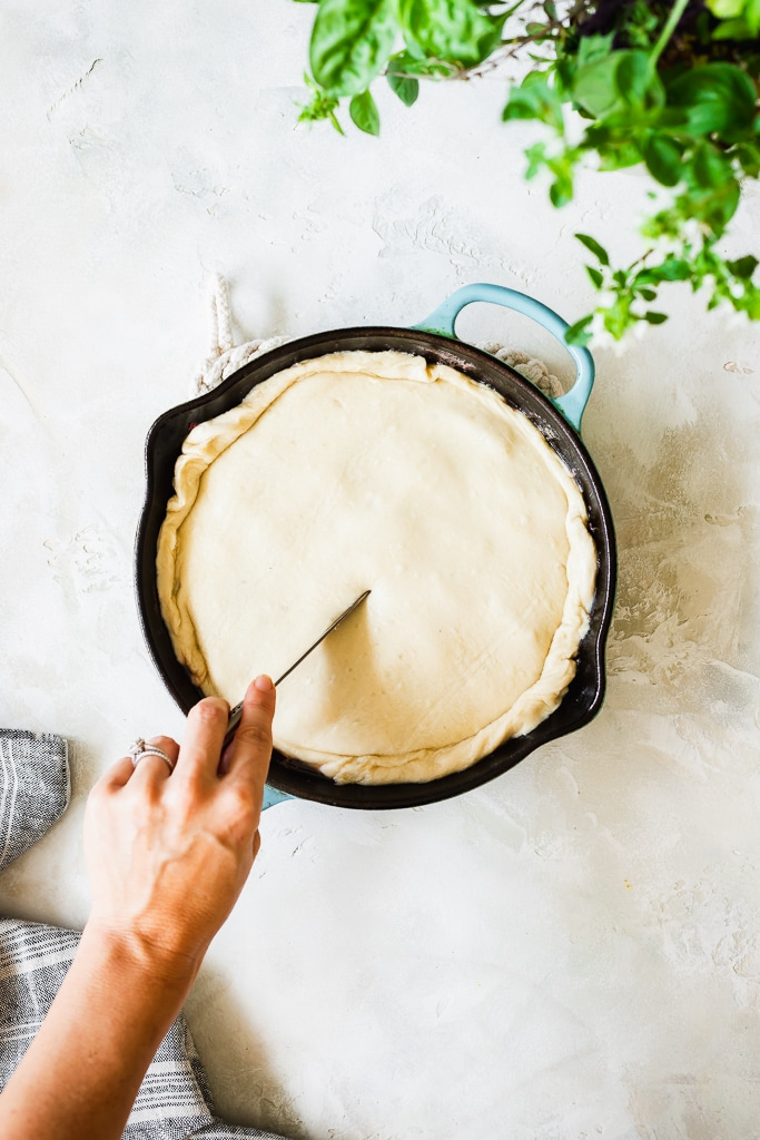 a woman cutting some slits in the puff pastry crust of a tarte tatin to allow steam to vent