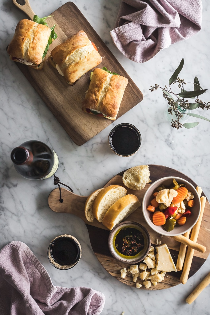 an overhead scene of a table with sandwiches, cheese board, bread and glasses of red wine
