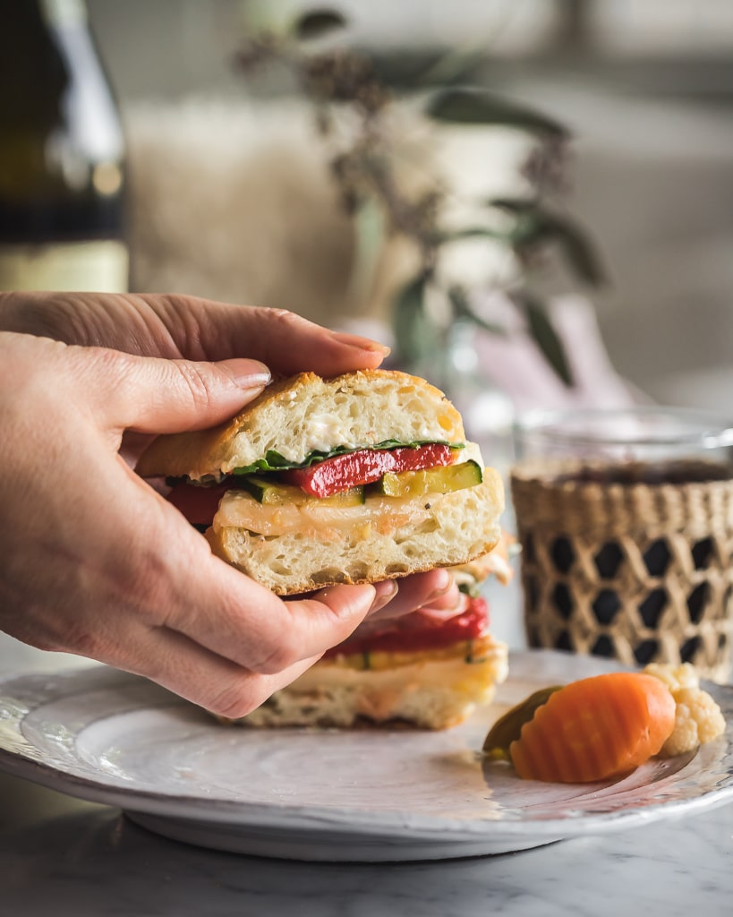 Hands holding a roasted vegetable sandwich