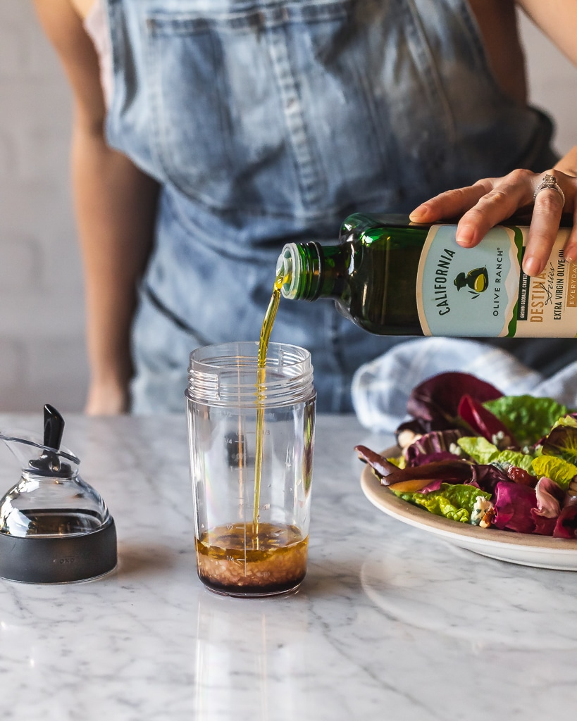 olive oil being poured into a salad shaker
