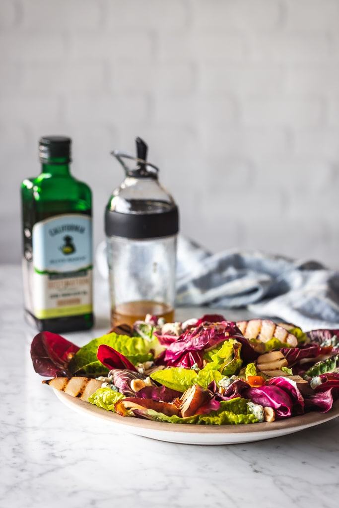 chicory salad on a plate with olive oil and salad dressing shaker in the background