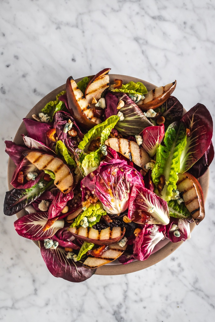 a bowl of chicory salad with grilled pears